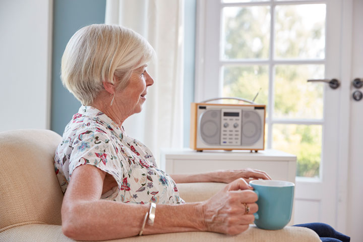 senior-woman-drinking-tea-and-listening-to-radio-PN5U2P7