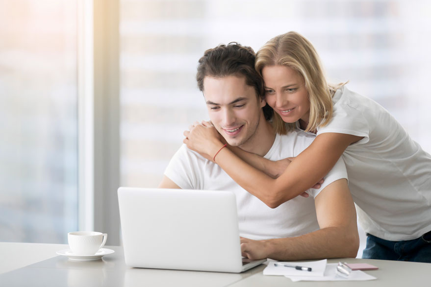 young-happy-couple-with-laptop-PBUA6YS